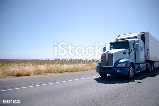 istock Big rig semi truck with stainless steel spoiler and reefer trailer on the road 696821020
