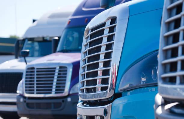 Big rig semi trucks tractors grilles in row on truck stop - foto stock