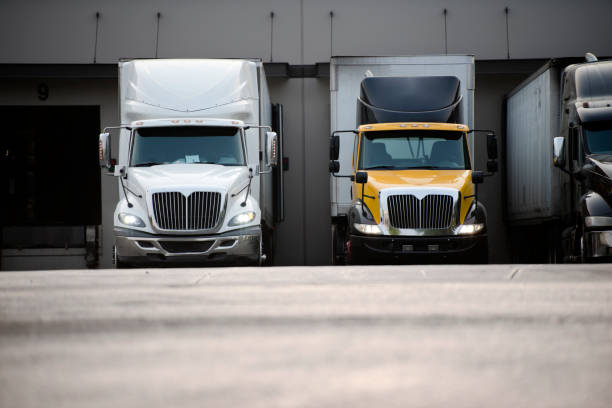 big rig semi trucks with semi trailers standing in warehouse dock for loading commercial cargo - lorries unloading stock photos and pictures