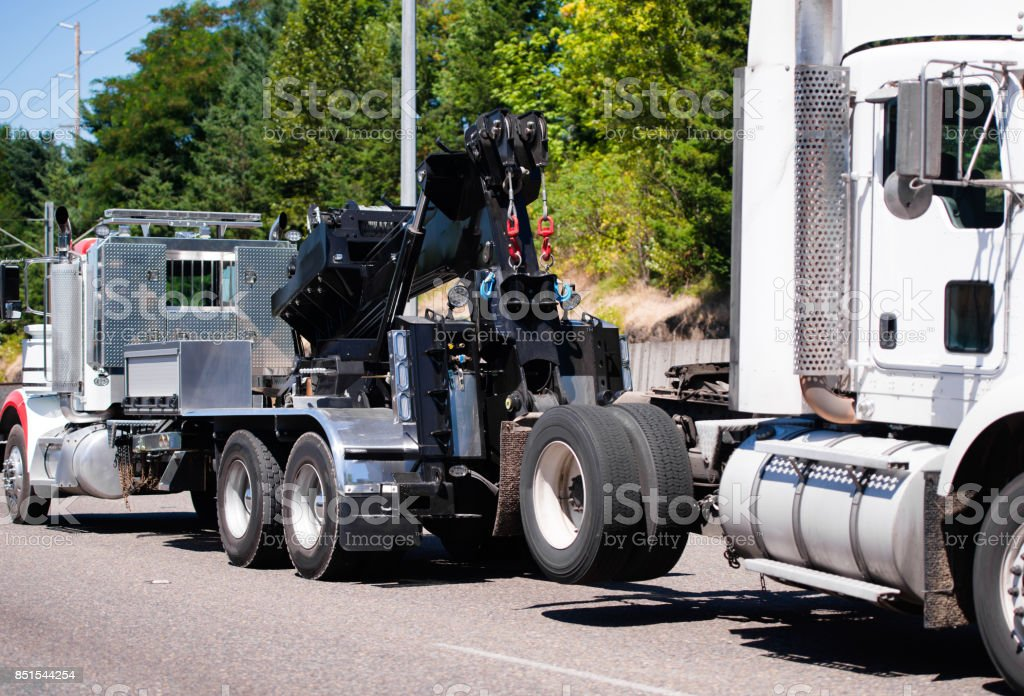 Big rig towing semi truck tow ather semi truck tractor on the road stock photo