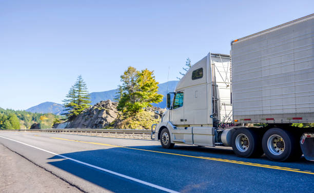 Big rig white bonnet long haul semi truck transporting frozen food in refrigerator semi trailer running on the road in Columbia Gorge stock photo
