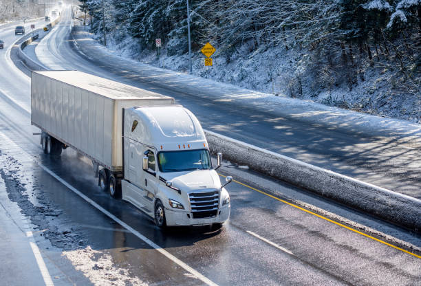 Big rig white bonnet semi truck with dry van semi trailer moving on the winding winter road with wet surface and snow stock photo