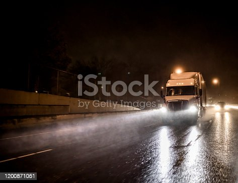Big powerful bonnet rig industrial grade semi truck with loaded semi trailer transporting commercial cargo running at night time with turned on headlights on the wet raining road with reflection