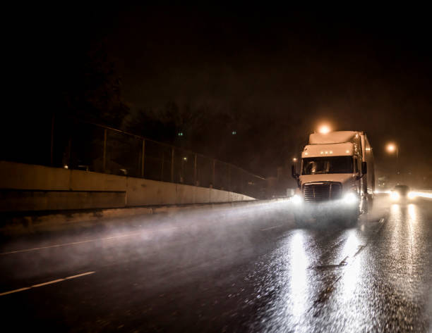 Big rig white semi truck transporting cargo in semitrailer driving on the night wet road with heavy rain and water dust stock photo