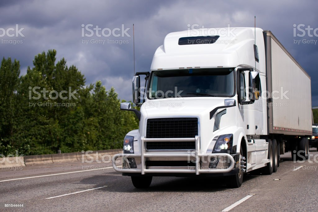 Big rig white semi truck with grille guard and trailer on the road stock photo