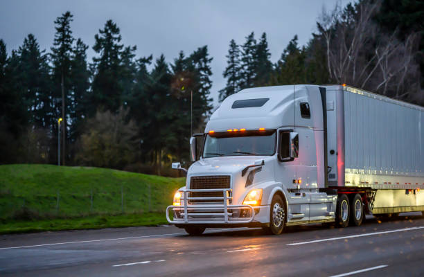 Big rig white semi truck with grille guard transporting cargo in dry van semi trailer running on the evening road with turned on headlights stock photo
