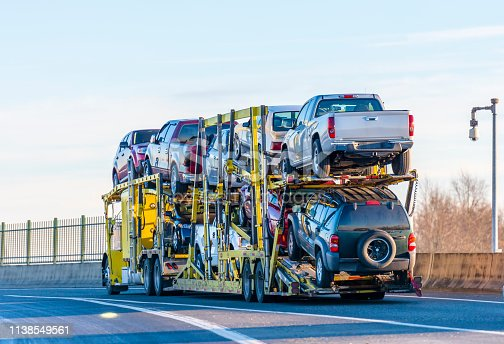 Big rig industrial grade yellow classic bonnet car hauler semi truck transporting cars on two levels semi trailer driving on the overpass road with protective fence on the side