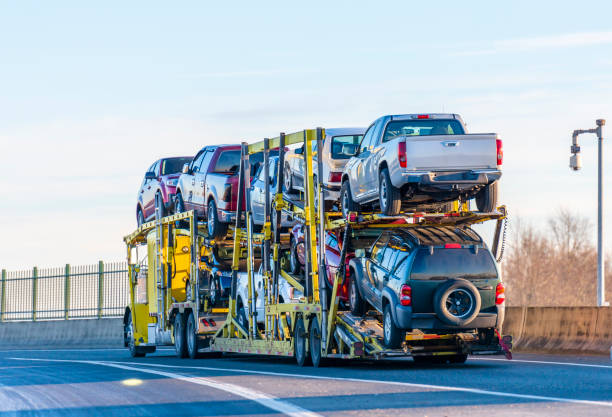 Big rig yellow car hauler semi truck transporting cars on two levels semi trailer driving on the overpass road stock photo