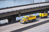 Big rig yellow tipper semi truck with dump trailer running on overpass intersection road along the river