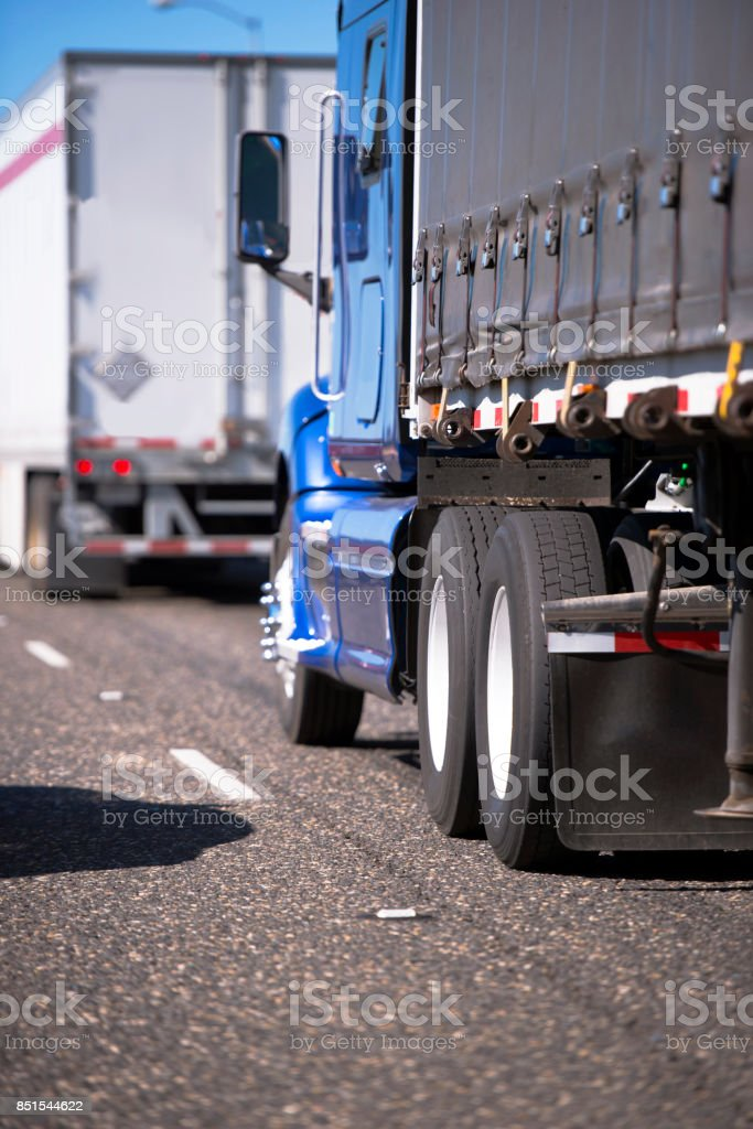 Big rigs semi trucks convoy with different trailers for long and local haul delivering commercial cargo stock photo