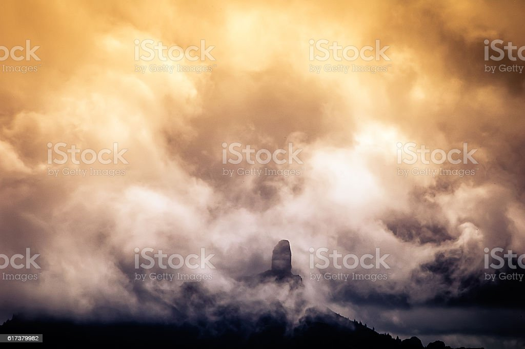 Big rock surrounded by clouds at sunset stock photo