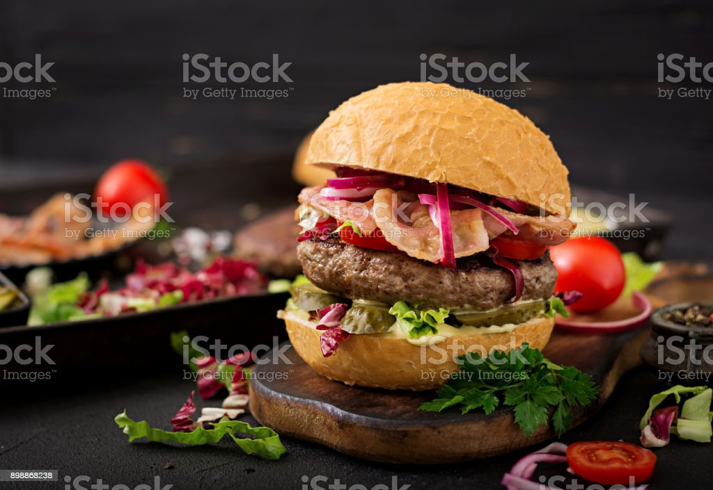 Big sandwich - hamburger burger with beef,  tomato, pickled cucumber and fried bacon stock photo