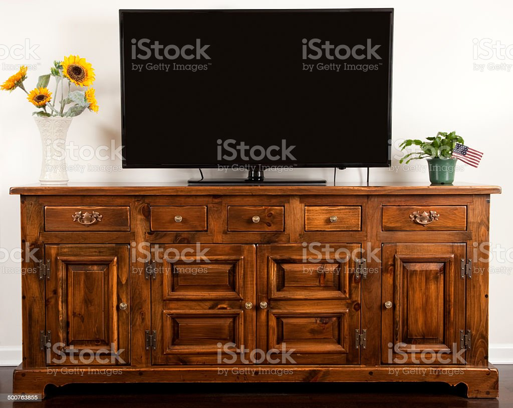 Big Screen TV sitting a colonial style wood cabinet stock photo