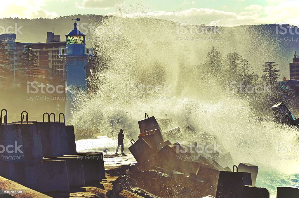 Big seas breaking over lighouse and sea wall stock photo