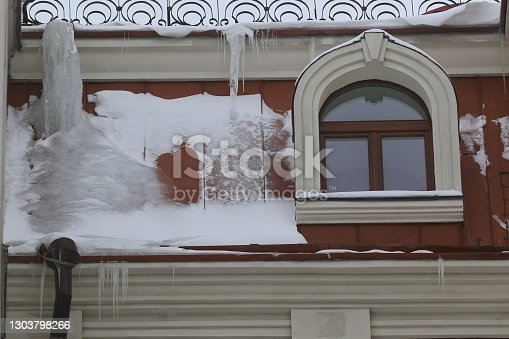 Big, sharp icicles and melted snow hanging from eaves of roof. Dangerous icicles on the roof. Danger of being near a building. City landscape.