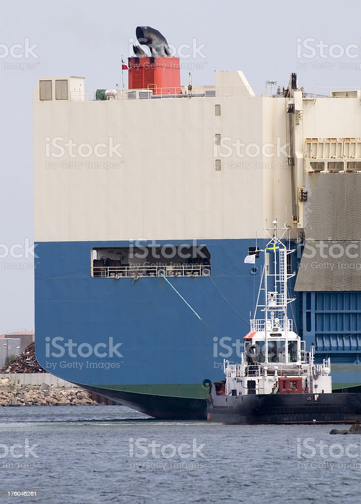Small tugboat guiding a huge car carrier ship to its docking in MalmA...