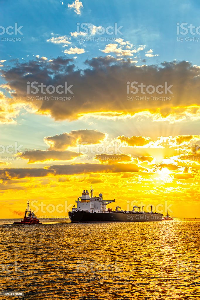 Big ship in the middle of the ocean with the sunrise behind stock photo