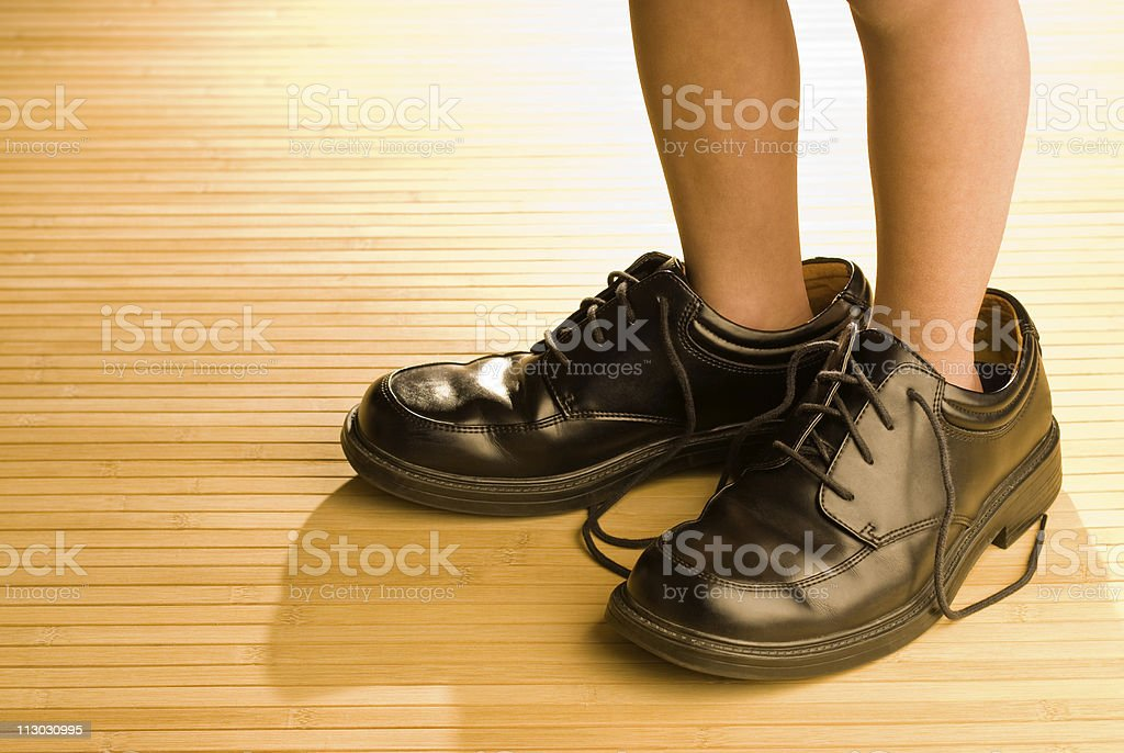 Big shoes to fill, child's feet in large black shoe royalty-free stock photo