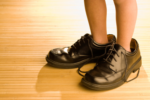 Big shoes to fill, child's feet in large black shoe stock photo
