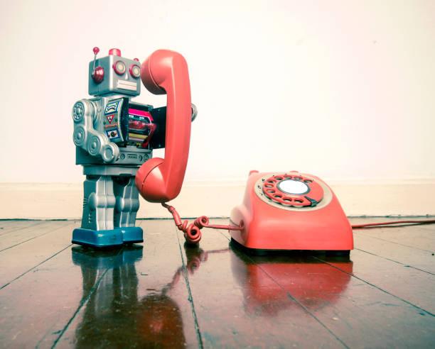 jouet robot argent gros relative au statut de téléphone sur un t de parquet ancien - chatbot photos et images de collection