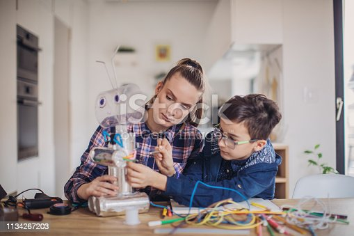 Young woman teacher and little boy, making together a robot from recycled materials, working on creative homework at home.