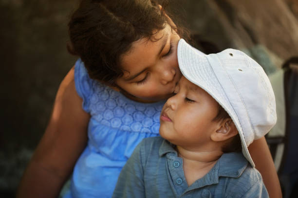 Big sister comforts her little brother after getting hurt outdoors, by giving him a kiss in the forehead. stock photo