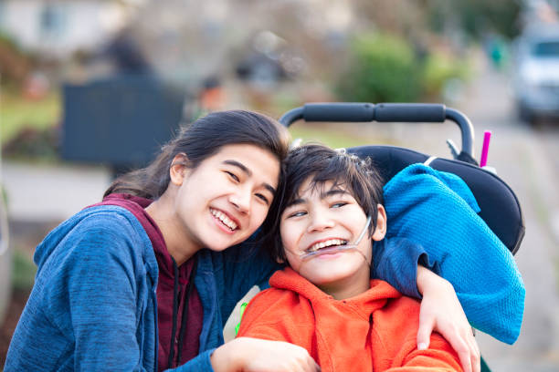 Big sister hugging disabled brother in wheelchair outdoors, smiling Biracial big sister lovingly hugging disabled little brother in wheelchairoutdoors, smiling persons with disabilities stock pictures, royalty-free photos & images