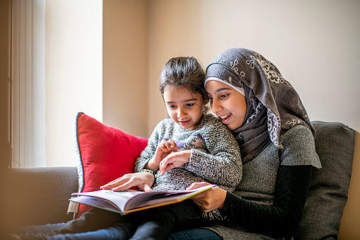 A pre-teen girl wearing a hijab sits on a couch with her little sister on her lap and reads her a bedtime story. Her sister is engaged in the story.