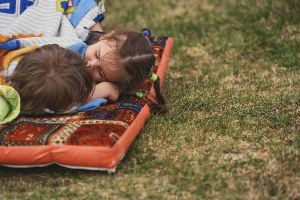 Big sister trying to put her little brother to sleep stock photo