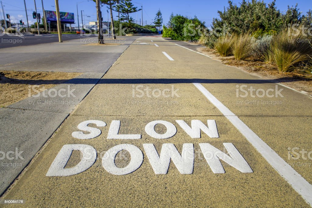 Big Slow Down sign on the footpath closeup stock photo