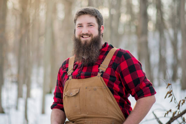 Big Smile An attractive lumberjack man sits in a winter wood. He is bearded, and wears red plaid and brown overalls. The sun shines as the man smiles widely at the camera. lumberjack stock pictures, royalty-free photos & images