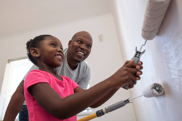 Big smiles as daughter helps father paint close up low angle view stock photo