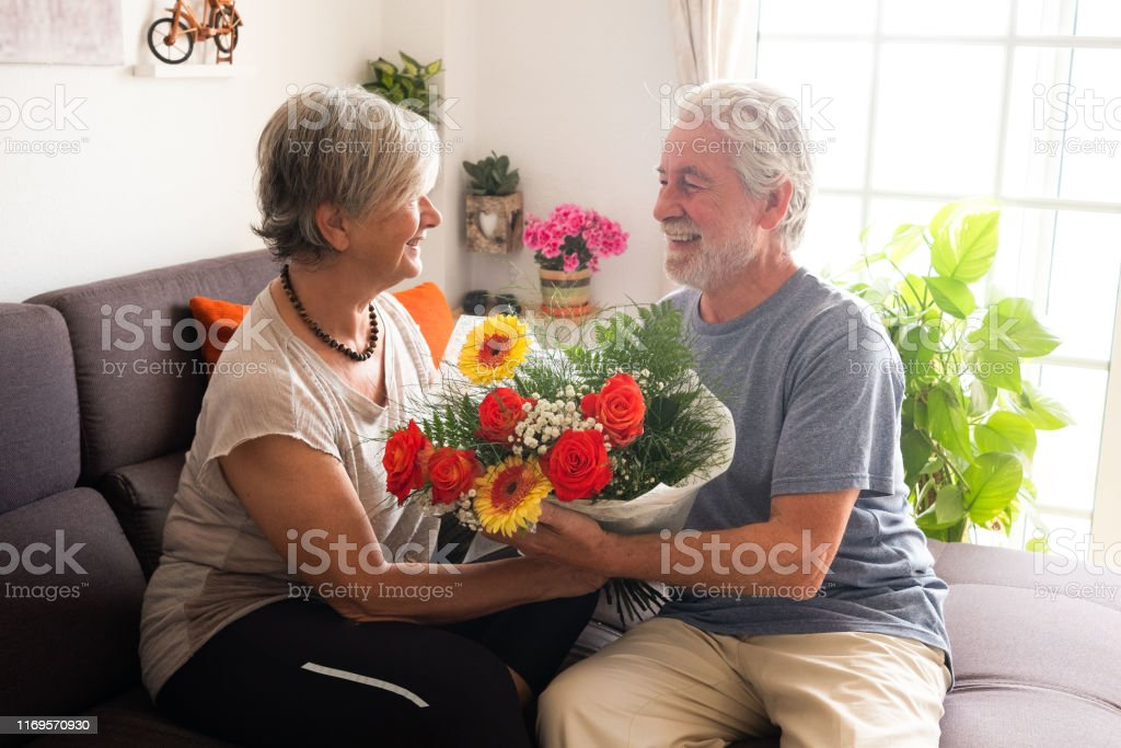 Big smiles for two senior people. Gift of bouquet of beautiful...