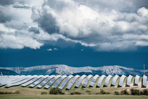 Big solar power plant with mountain ridge and dramatic clouds. Concept of environment protection and renewable energy generation to prevent climate change.