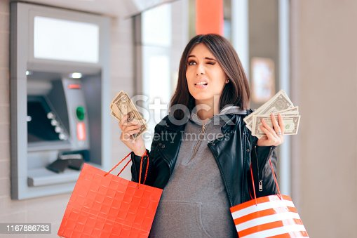 istock Big Spender Holding Money in front of the ATM 1167886733