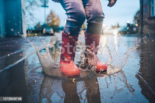 Little girl having fun in a puddle on a autumn rainy day in her pink boots