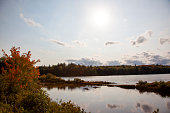 A beautiful lake with clouds and rocks among autumn trees in Canada
