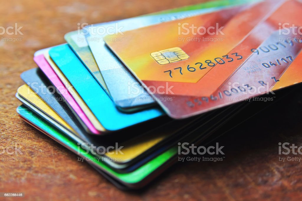 big stack of multicolored credit cards on a wooden
