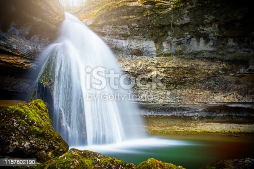Color photography of a beautiful big stalagmite natural column rock formation, with wild river flowing water waterfall in dark woodland in Bugey mountains in Ain, Auvergne-Rhone-Alpes region in France (Europe), near the small village of Surjoux.