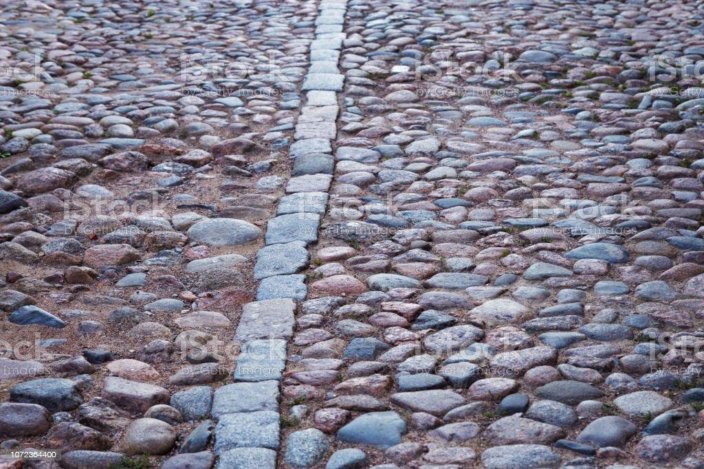 Big stones on ground close up. Cobblestone road. Large stones on...
