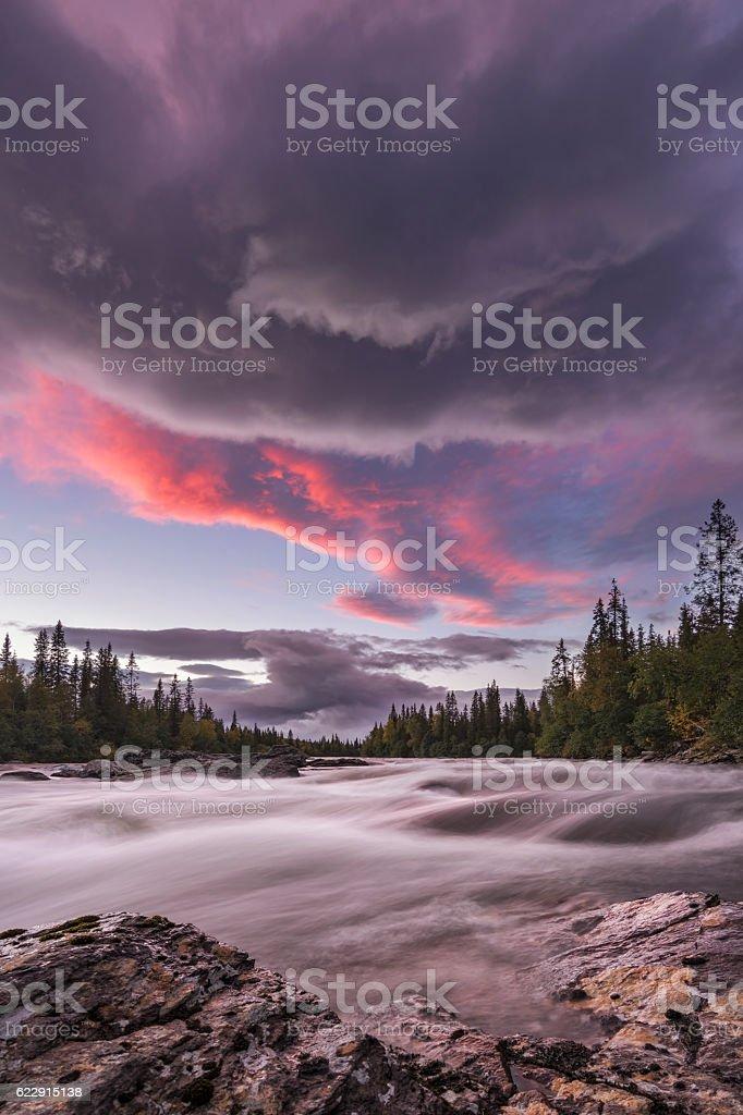 Big stream flowing in beautiful river scape pink orange sunset foto