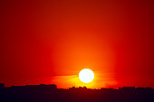 Big sun over the city in the evening . Sunset at red sky