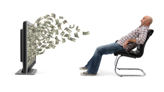 A man sitting on armchair and cash (one hundred-dollar bills) flowing out of a flat screen television. He is amazed and scared. Isolated on white background.