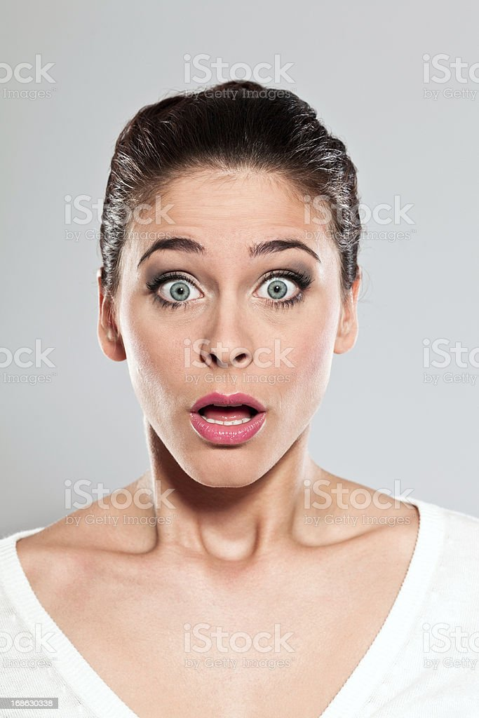 Big surprise Portrait of shocked young woman staring at the camera. Studio shot on a grey background. 20-24 Years Stock Photo
