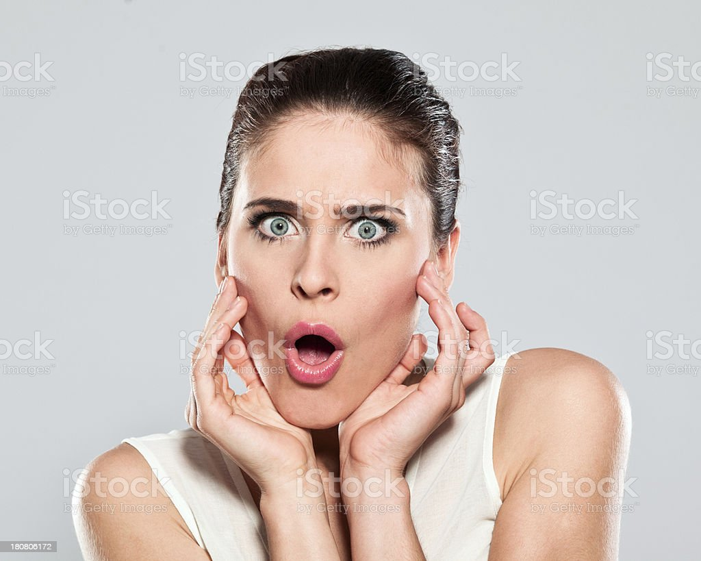 Big surprise Portrait of shocked young woman staring at the camera with mouth open. Studio shot on a grey background. 20-24 Years Stock Photo