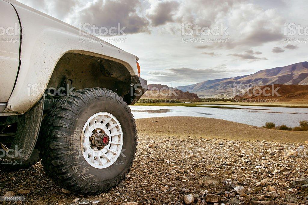Big SUV car wheel on backdrop of lake stock photo