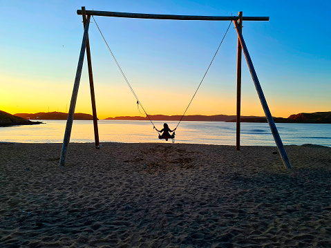 on a large swing, on the beach by the sea, a woman swinging at sunset