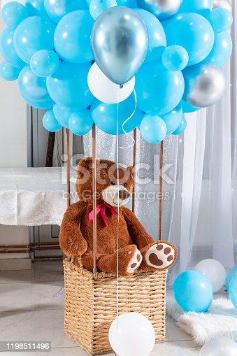 Beautiful big brown Teddy bear in the balloon basket with blue balloons. Kids blush bear toy sitting in a basket indoor. Children birthday decoration. Birthday party decoration concept