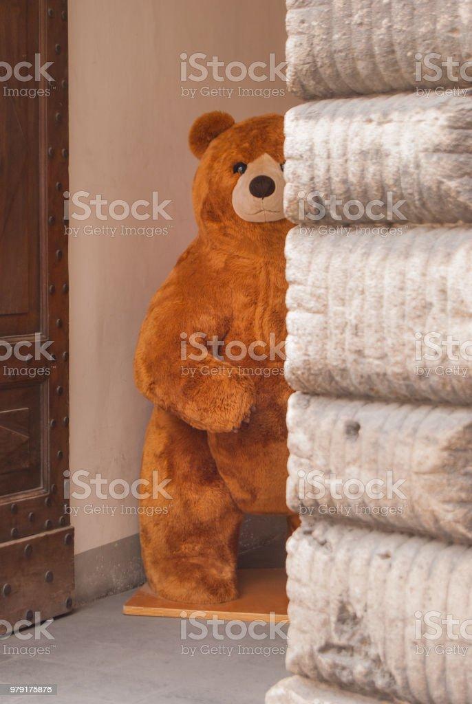 A big brown plush bear at an entrance
