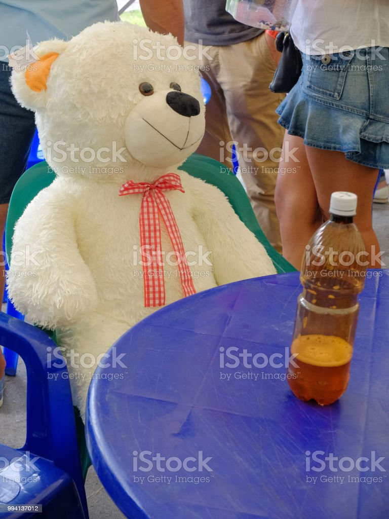 Big teddy bear sitting at a round table stock photo